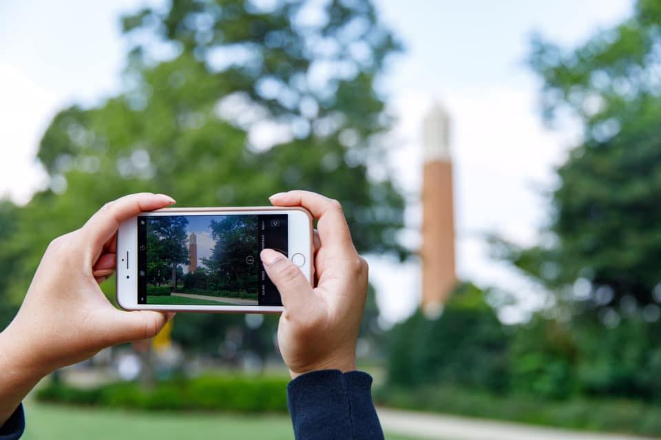 A student taking a photo of Denny Chimes with a phone.